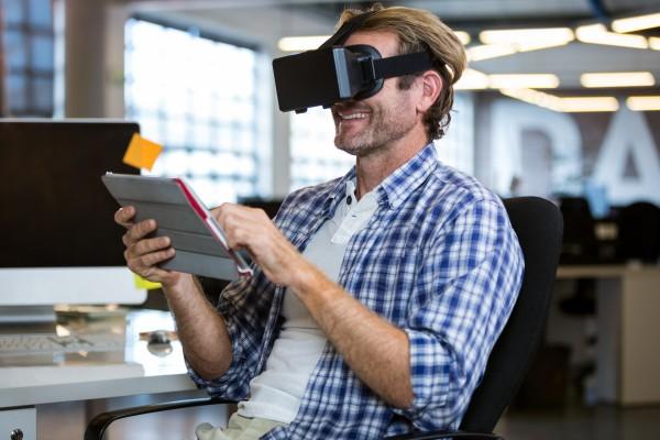 Happy creative businessman using virtual reality simulator in office