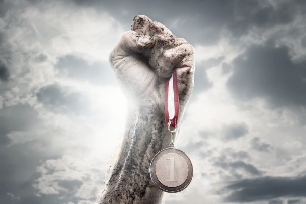 Male hand holding gold medal against the dramatic sky